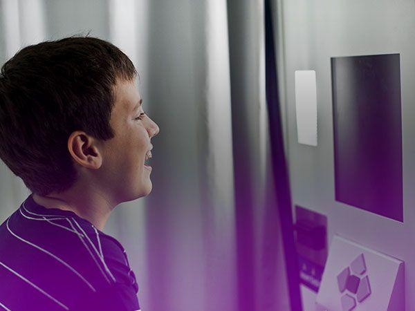 Un enfant sourit face à l'objectif d'une cabine automatique de photos