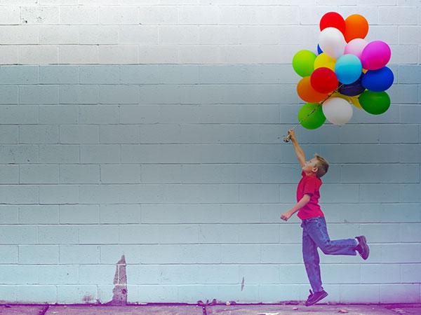 Un enfant s'amuse avec une grappe de ballons de baudruches