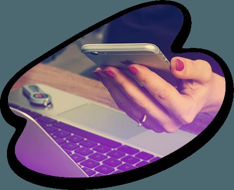 Une femme regarde son smartphone pendant qu'elle utilise son ordinateur