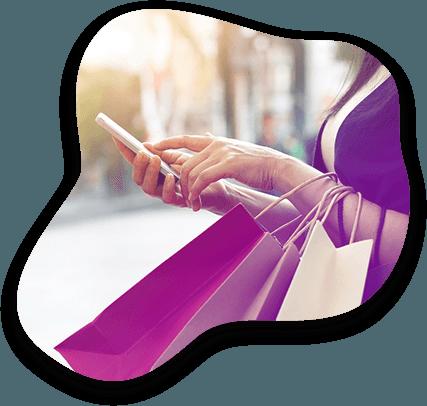 Une femme consulte son smartphone et transporte des achats dans des sacs