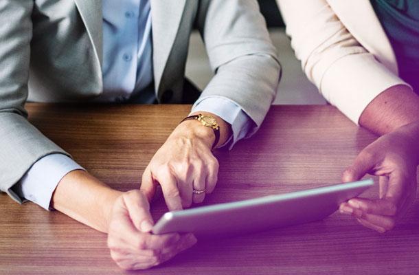 Une commerciale Adrexo présente un nouveau service à un client sur une tablette numérique