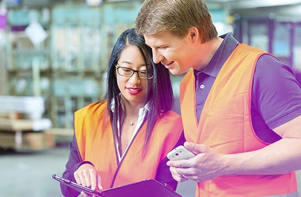 Deux responsables logistiques Adrexo suivent la distribution d'une campagne grâce à une tablette numériques